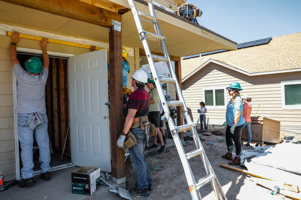 Workers move along the house for Habitat for Humanity's work day Thursday in Gypsum.