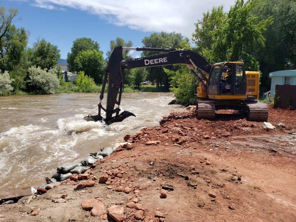 A backhoe places large boulders in the Eagle River to stabilize the area near Riverview Mobile Home residences/