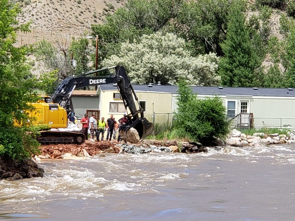 Heavy equipment and a sandbag crew work to stabilize the Eagle River bank at the Riverview Mobile Home Park in Gypsum Tuesday.