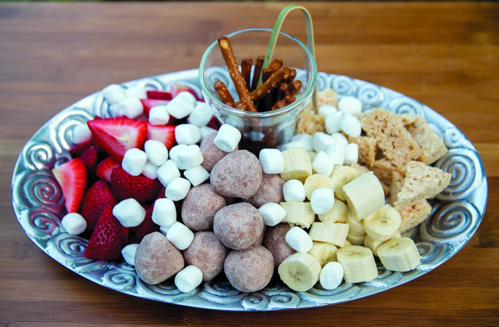 Fondue at Home dessert includes a pot of melted Belgium chocolate along with a selection of sweet treat to dip in the pot, like fresh strawberries, rice crispy treats and marshmellows.