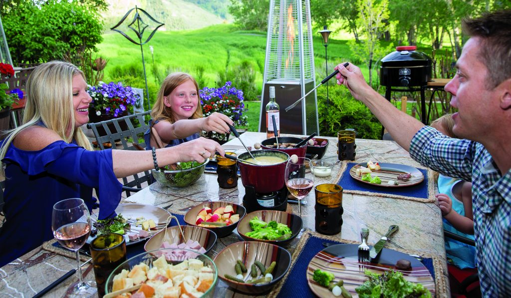 Fondue at Home offers the perfect summer at-home catered meal, with a melted cheese pot along with a hot pot of beef broth that stays warm as the even outside cools off along with plenty of meat, bread and vegetable options to dip in the fondue.
