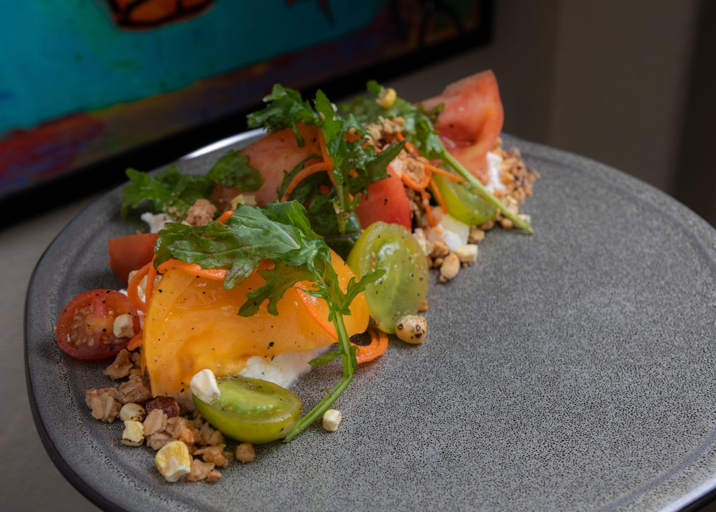 Heirloom Tomato | house cheese, sea beans, corn, smoked almond granolla, cider dressing from La Tour in Vail.