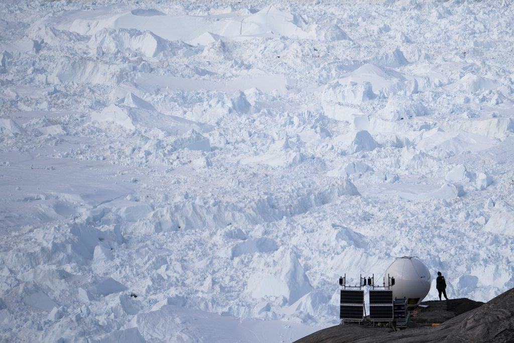 In this Aug. 16, 2019, photo, a woman stands next to an antenna at an NYU base camp at the Helheim glacier in Greenland. Summer 2019 is hitting the island hard with record-shattering heat and extreme melt. Scientists estimate that by the end of the summer, about 440 billion tons of ice, maybe more, will have melted or calved off Greenland's giant ice sheet. (AP Photo/Felipe Dana)