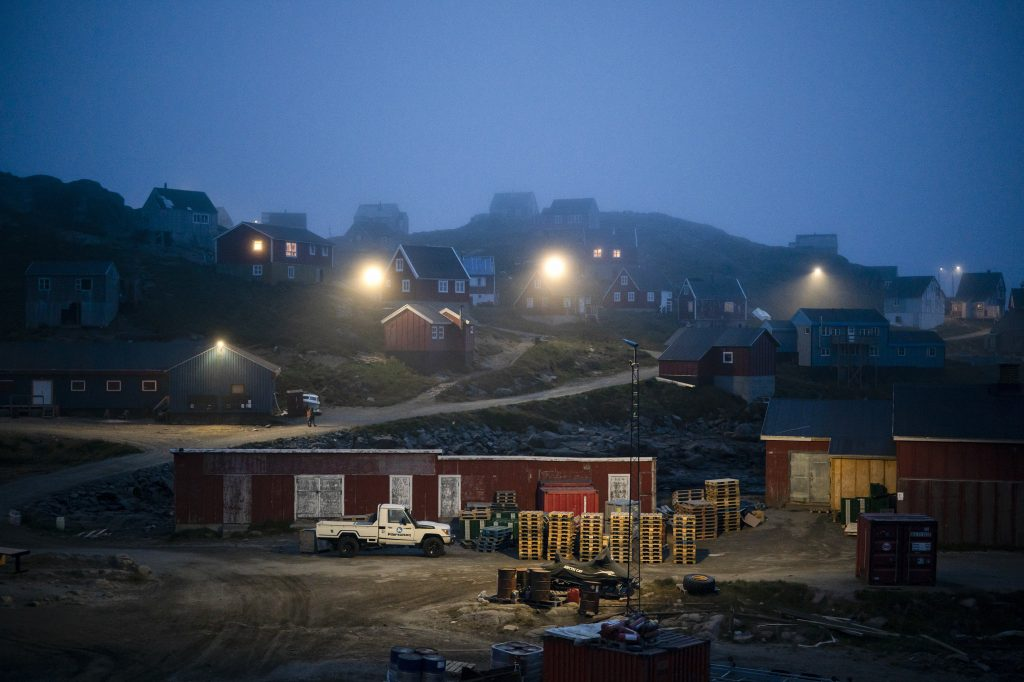 In this Aug. 15, 2019, photo, early morning fog shrouds homes in Kulusuk, Greenland. In tiny Kulusuk, resident Mugu Utuaq says the winter that used to last as long as 10 months when he was a boy, can now be as short as five months. Scientists are hard at work in Greenland, trying to understand the alarmingly rapid melting of the ice. (AP Photo/Felipe Dana)