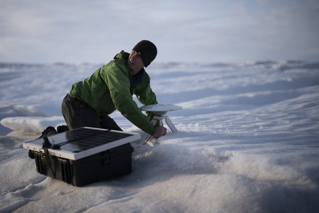 In this Aug. 16, 2019, photo, Brian Rougeux, NYU Field Safety Officer, installs a GPS antenna at the Helheim glacier, in Greenland. An NYU team is tracking what's happening in Greenland from both above and below. The head of the New York University team, air and ocean scientist David Holland, calls Greenland