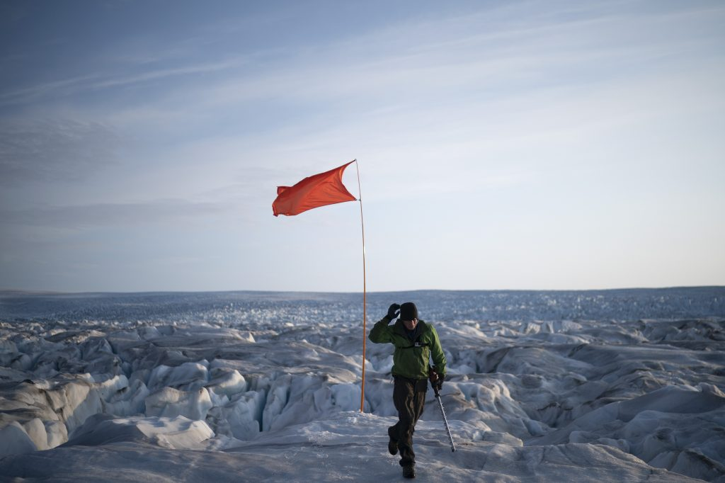 In this Aug. 16, 2019, photo, Brian Rougeux, NYU Field Safety Officer, walks after installing a flag to help identify a GPS position at the Helheim glacier, in Greenland. Summer 2019 is hitting the island hard with record-shattering heat and extreme melt. Scientists estimate that by the end of the summer, about 440 billion tons of ice, maybe more, will have melted or calved off Greenland's giant ice sheet. Helheim glacier has shrunk about 6 miles (10 kilometers) since scientists visited in 2005. (AP Photo/Felipe Dana)