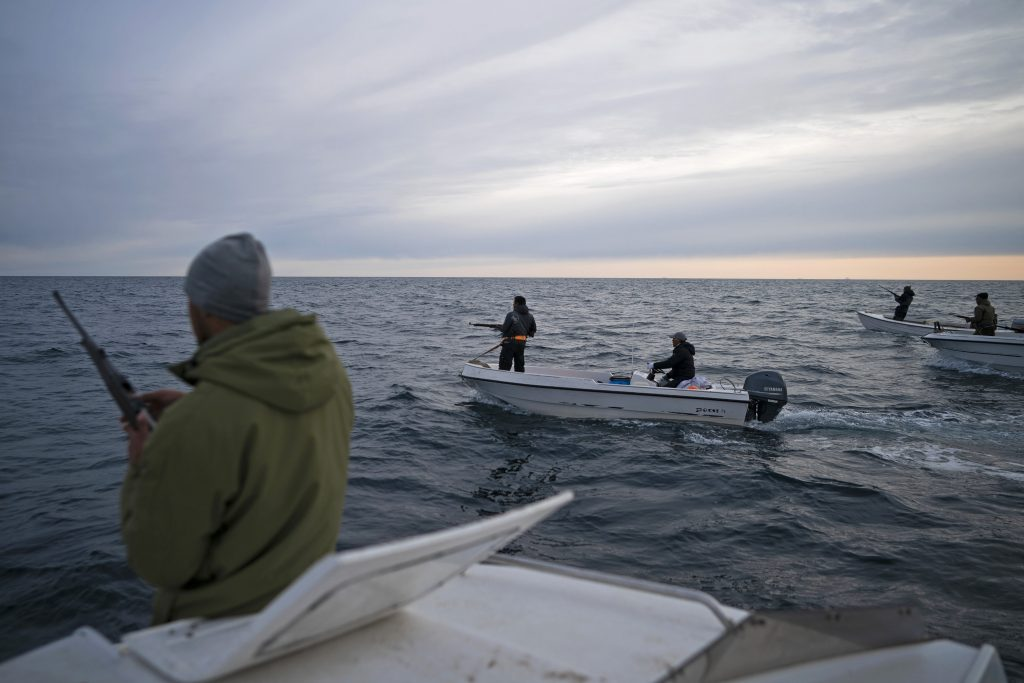 In this Aug. 16, 2019, photo, Mugu Utuaq, left, reloads his rifle as he rides with other boats hunting whales near Kulusuk, Greenland. Summer in 2019 is hitting the island hard with record-shattering heat and extreme melt. Scientists estimate that by the end of the summer, about 440 billion tons of ice, maybe more, will have melted or calved off Greenland's giant ice sheet. (AP Photo/Felipe Dana)