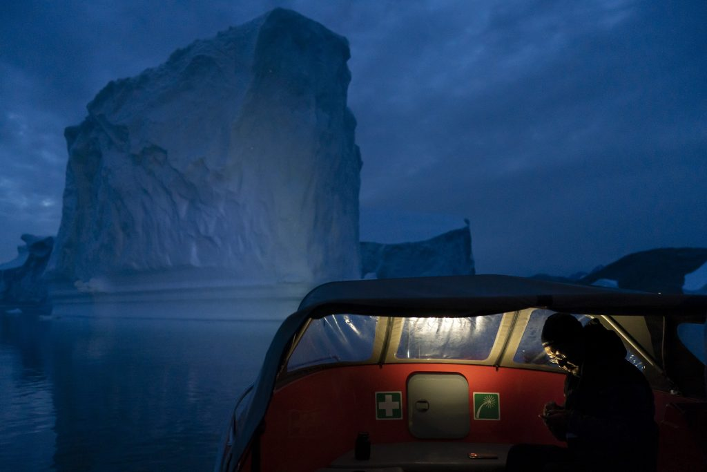 In this Aug. 15, 2019, photo, a boat navigates at night next to a large iceberg in eastern Greenland. Summer 2019 is hitting Greenland hard with record-shattering heat and extreme melt. By the end of the summer, about 440 billion tons (400 billion metric tons) of ice, maybe more, will have melted or calved off Greenland's giant ice sheet, scientists estimate. (AP Photo/Felipe Dana)