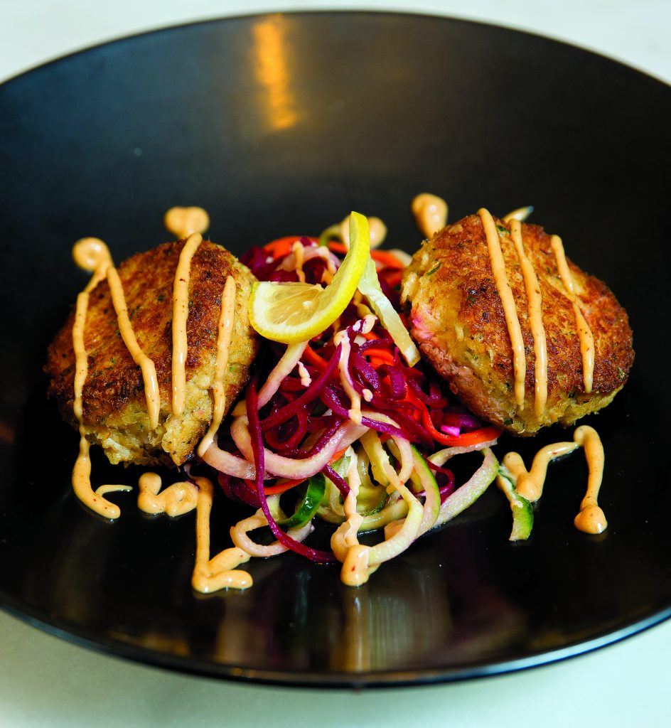 Crab Cakes: Home made jumbo lump crab cakes, mixed vegetable salad, finished with a chipotle aioli.