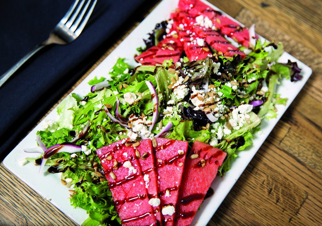 Summer Watermelon Salad: Fresh watermelon, mixed greens, red onion, goat cheese, citrus vinaigrette, finished with balsamic reduction.