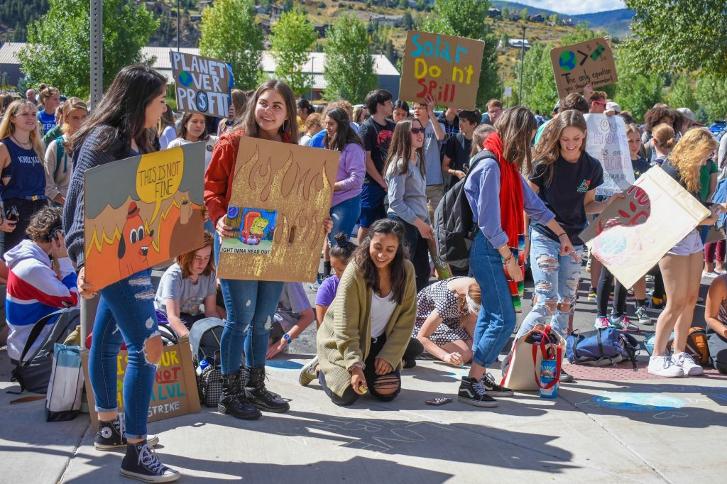 Students hold up signs during Friday's protest at Battle Mountain that coincided with worldwide strikes demanding action on climate change.