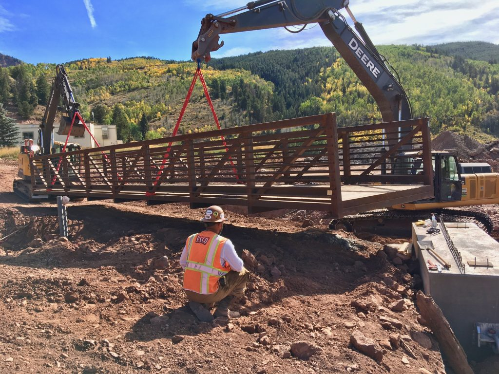 A spotter makes sure the new Sylvan Lake pedestrian bridge is perfectly placed.