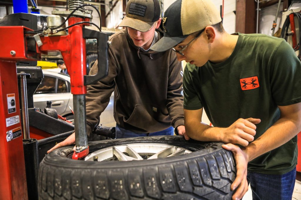 Nick Wagner and Branden Vigil remove a tire during auto shop class Wednesday, Oct. 30, in Gypsum. Students learn everything from basic car maintenance to advanced maintenance depending on the class.