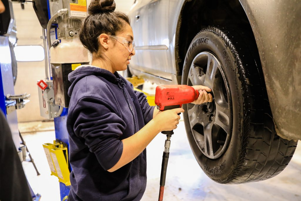 Kalie Roybal removes the wheel to replace the tires Wednesday, Oct. 30, at the Spring Creek Campus in Gypsum.