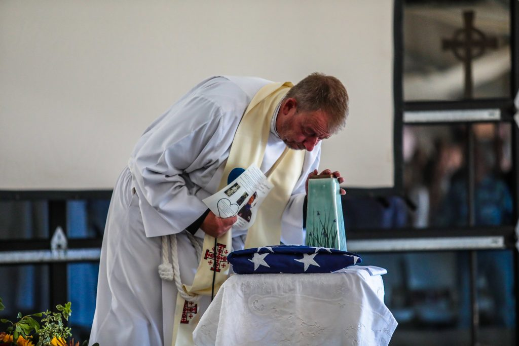 Reverend Stuart Brooks Keith pays his respects to friend Sandy Treat Tuesday at 4 Eagle Ranch in Wolcott.
