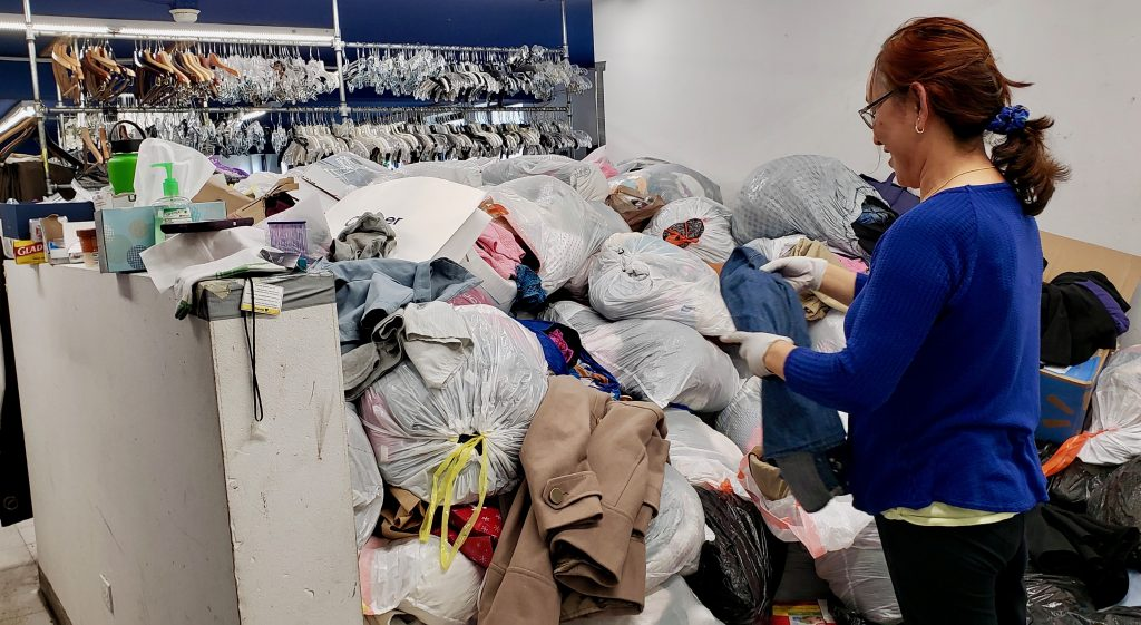 Thrifty Shop employee Peme Danore shifts through bags piled up in the donation room.