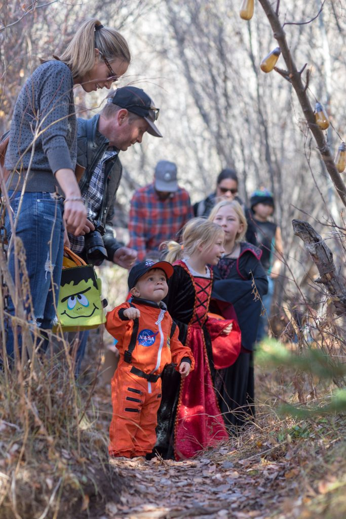 Kids in costumes walk through the woods at Fright at the Museum, an annual event held at the Walking Mountain campus in Avon.