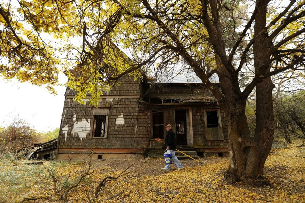 David Benscoter walks past an abandoned home on a remote homestead near Pullman, Wash., after collecting apples from the large orchard on the site.
