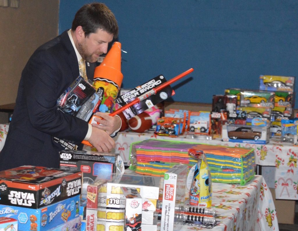 Aaron Greenier with Eagle's Masonic Lodge helps set up the Lodge's annual Toy Store. The Masons give away toys each Christmas to kids who need them.
