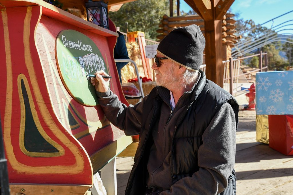 Kristof Kozmowski sketches outlines before doing touch-up paint work to Santa's sleigh at Glenwood Caverns Adventure Park in preparation for Winter on the Mountain.