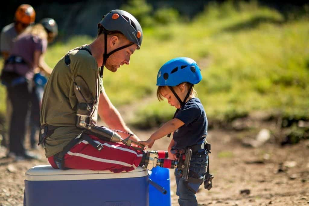Jason Hallett gets a little help from his son as they prepare to do some rock climbing as part of a Vail Veterans Program's summer family session.