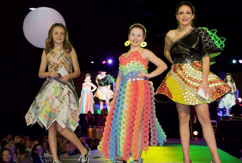Winning designs of the ages 13 - 18 category take a walk on the runway at Project Funway. Teen winners, from left, were Annika Bettenhausen and Isabella Borg, modeled by Borg (dyed newspaper), Lisa Overy (pool noodles), and Valentina Campos (innertube, bottle caps, 6-pack holders).
