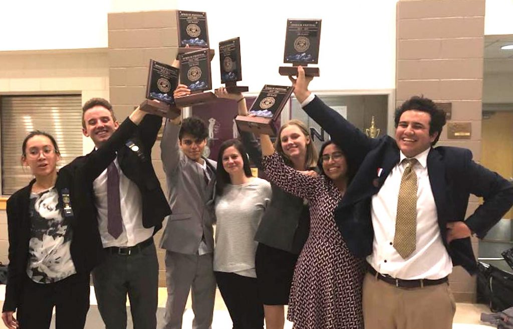 Eagle Valley's state speech tournament winners hoist their hardware. That's coach Katie Uhnavy in the middle.