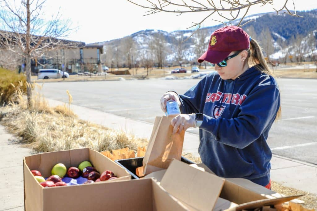 Ashley Rozzi, Assistant Manager of Nutrition Service Area Operations, packs bag lunches Monday in the parking lot of Battle Mountain High School in Edwards. Businesses like Yeti's Grind is donating milk to the operation, which otherwise would go bad.