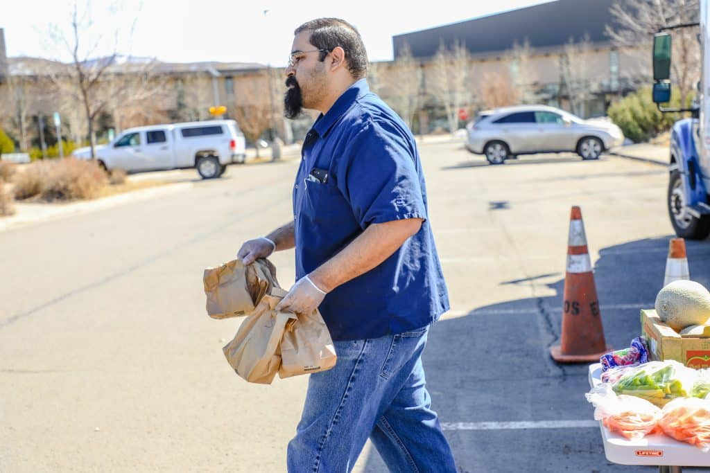 Tony Cardona, nutrition service area Ooperations manager for Eagle County Schools, walks sack lunches to cars in Edwards. Lunch pick up is available 11 a.m. to 1 p.m., Monday through Friday.