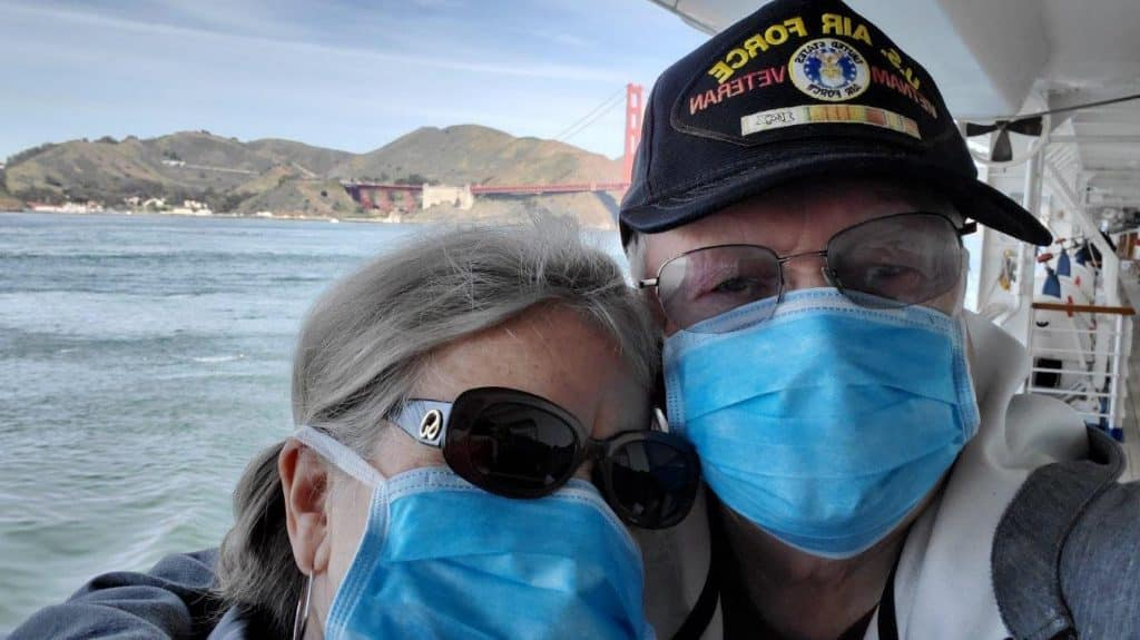 Bonnie and Buddy behind their masks and in front of the Golden Gate Bridge, aboard the Grand Princess.