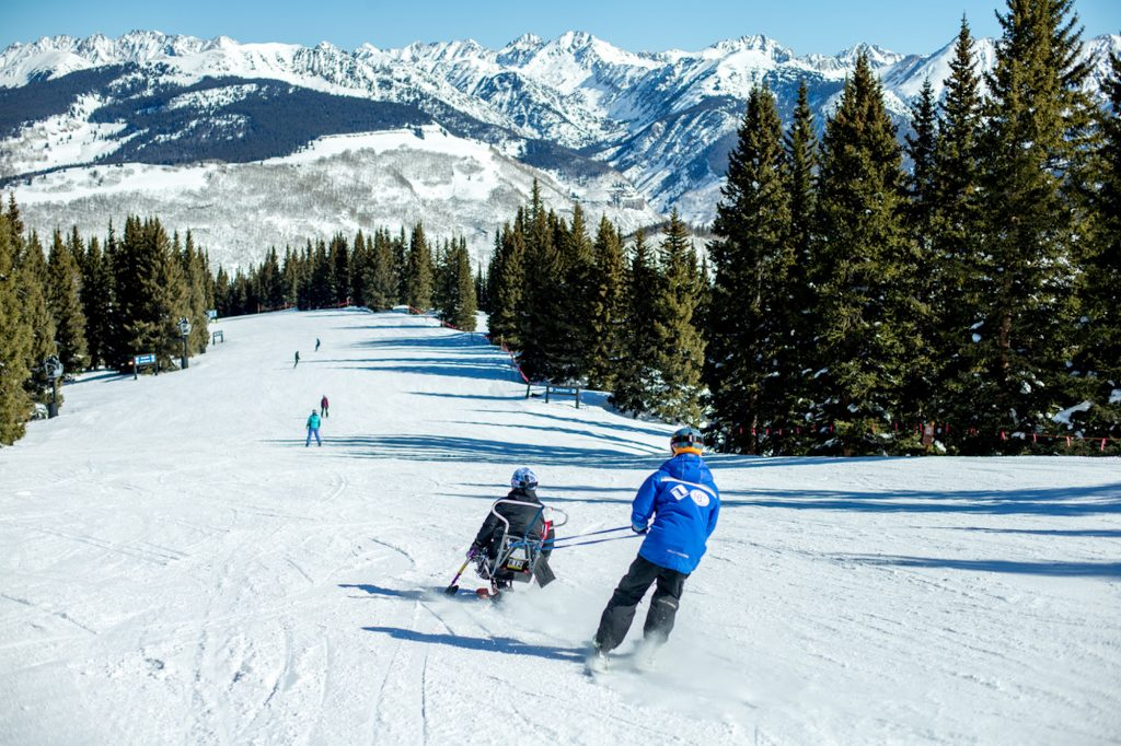 Instructor Scott Giffin helps veteran Dez Delbarba down a run in Vail on a bluebird day.