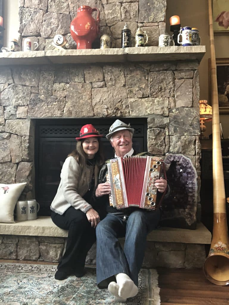 """Helmut Fricker and fiancée Charlotte Bogert pose in front of Fricker's """"stage"""" for his Friday shows. Fricker said his most popular song requests on Facebook Live are """"Edelweiss"""" and """"The Happy Wanderer."""""""