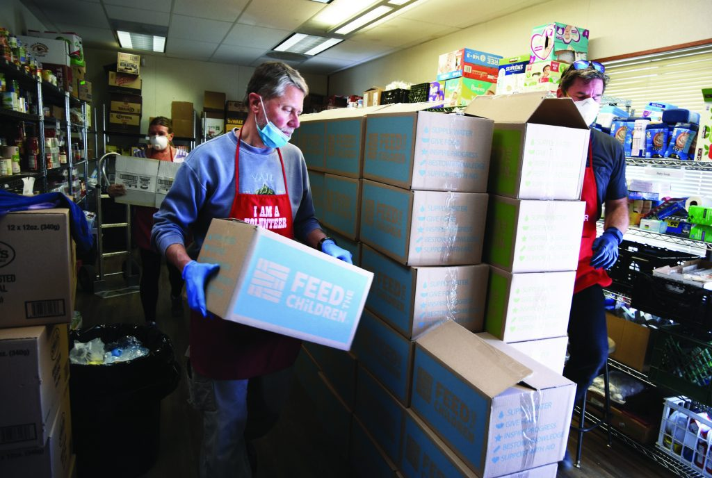 Pastor Scott Beebe, center, adds a box filled with food to a stockpile Tuesday at the Salvation Army in Avon. The Salvation Army is handing out food to any community member in need, feeding people in isolation due to COVID-19 and providing food for ambulance crews.