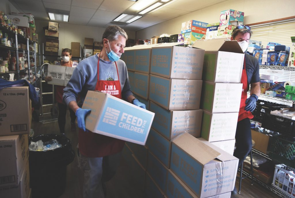 The Salvation Army received a $20,000 grant from the Vail Rotary Club, as did Our Community Market. Both have been hammered by increased requests for food assistance from local residents. Rotarian and volunteer Scott Beebe, center, adds a box filled with food to a stock pile at Avon's Salvation Army center.