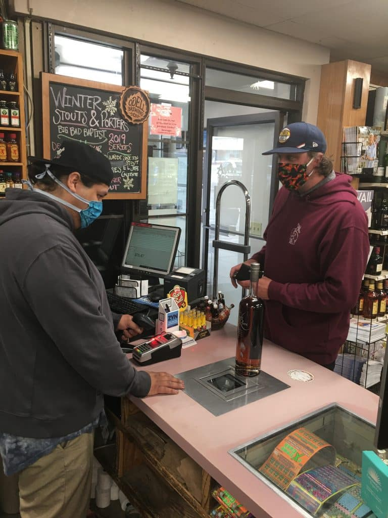 An Avon Liquor employee and customer conduct a recent masked transaction. The liquor store has been open during the initial phase of COVID-19 pandemic and will soon be joined by other businesses as Eagle County transitions its COVID-19 response.