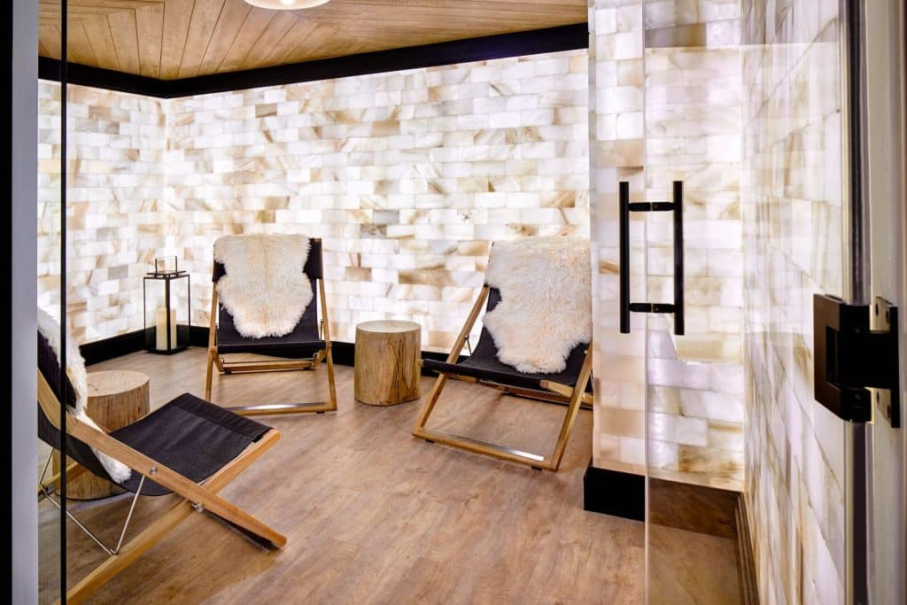 Relax in Well & Being Spa's salt therapy lounge surrounded by the calming glow of Himalayan salt blocks.