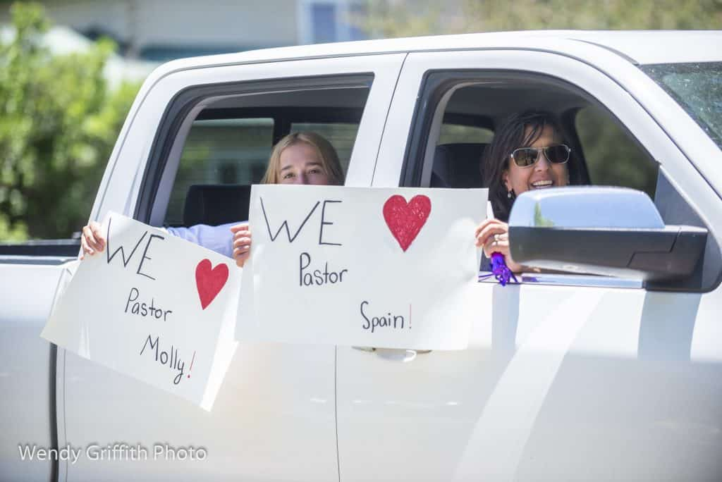 Eagle United Methodist members wave signs during the Jun 14 parade honoring Sid Spain and Molly Fiore.