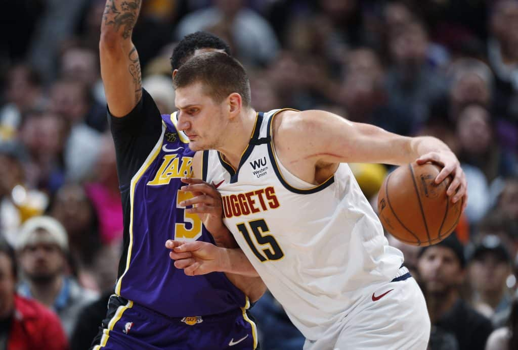 Denver Nuggets center Nikola Jokic drives as Los Angeles Lakers forward Anthony Davis defends during the first half of an NBA basketball game in Denver. A person with knowledge of the situation says Jokic has tested positive for the coronavirus and is quarantining in his native Serbia. (AP Photo/David Zalubowski, File)