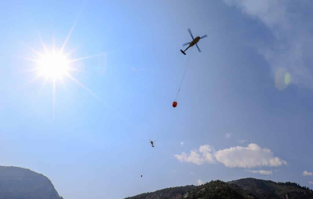 Helicopters come and go with slurry and water to fight the Grizzly Creek Fire Sunday near Glenwood Springs. The helicopters carry 750-gal buckets.