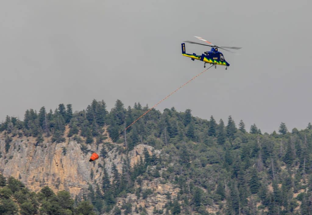 Helicopters fill with water from the Colorado River to fight the Grizzly Creek Fire Sunday near Glenwood Springs. Multiple helicopters were fighting the fire in the No Name drainage to prevent a western spread.