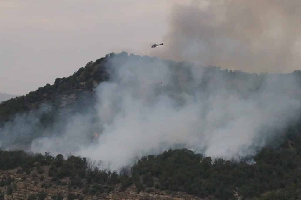 A helicopter circles over a wildfire near Wolcott.