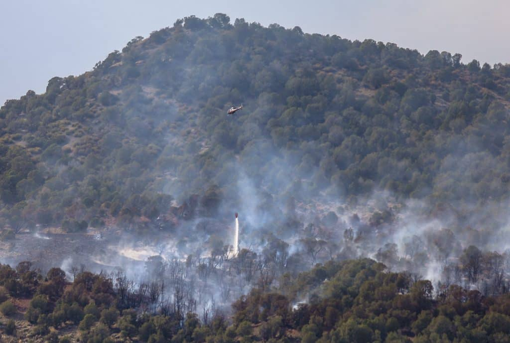 A helicopter drops water on smoldering trees Thursday near the Rube Creek Fire in Wolcott.