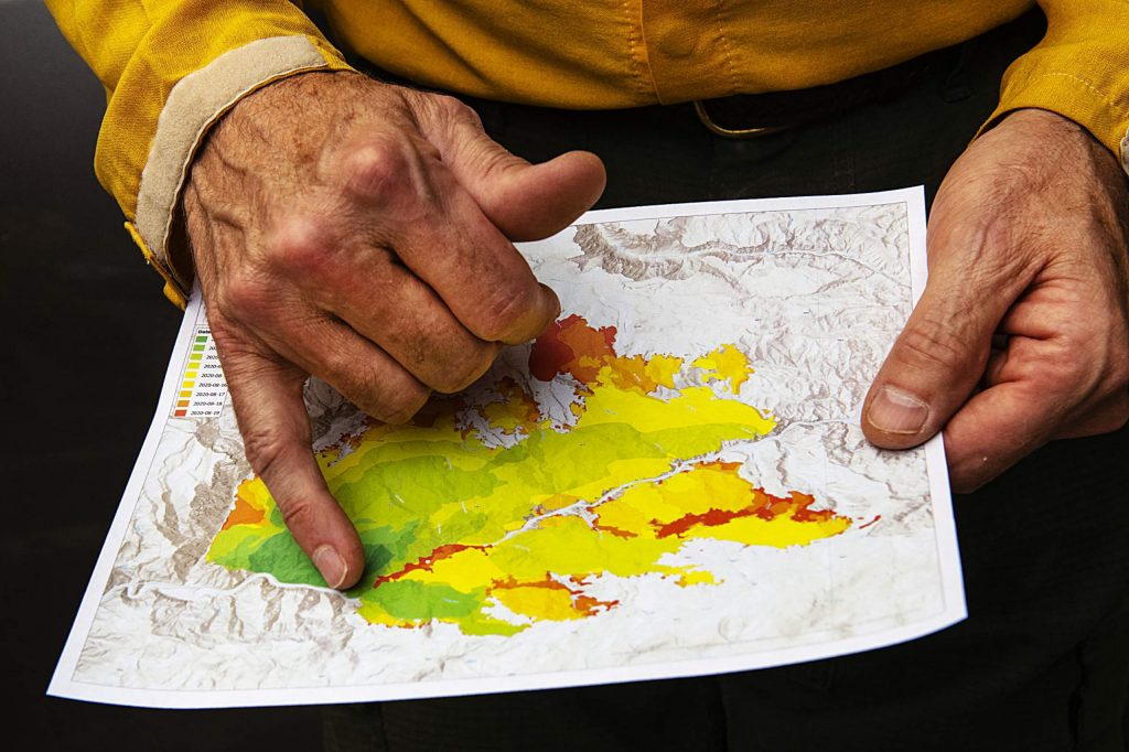 Wayne Patterson explains the timeline of the spread of the fire on Thursday, August 20, 2020. The green areas are the original burn and the darkest red is the new burn spots.(Kelsey Brunner/The Aspen Times)