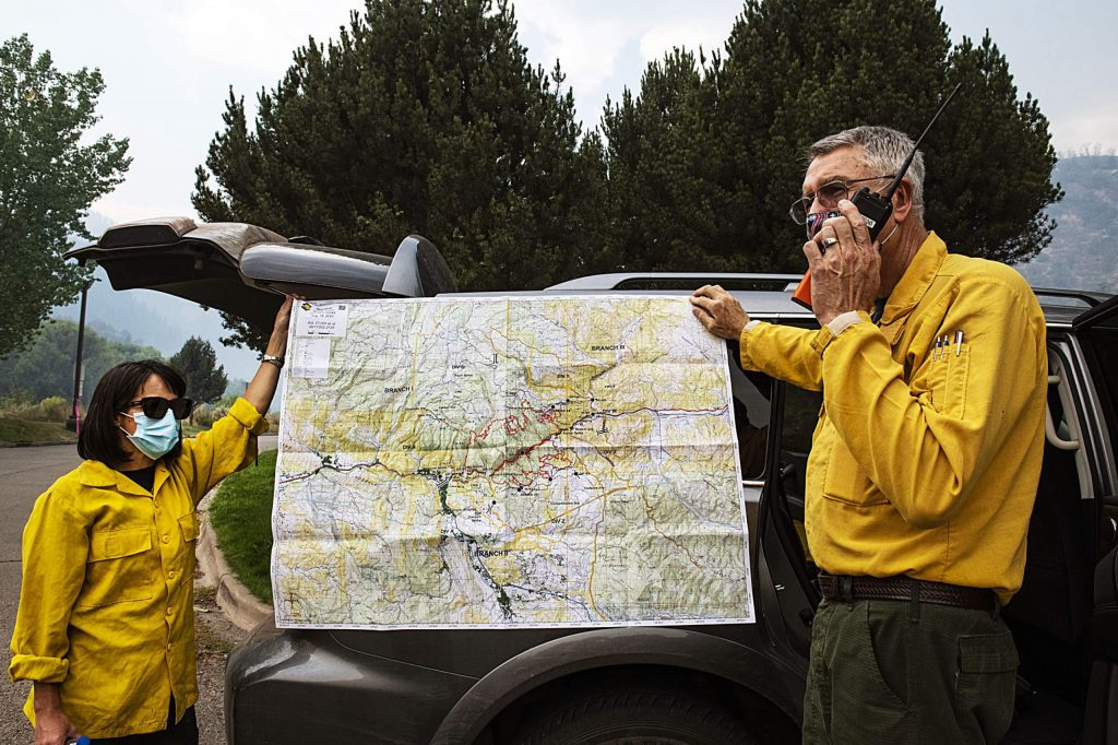 Wayne Patterson, left, talks in a walkie talkie while holding a perimeter map with Mina Bolton for the Grizzly Creek Fire on Thursday, August 20, 2020. (Kelsey Brunner/The Aspen Times)