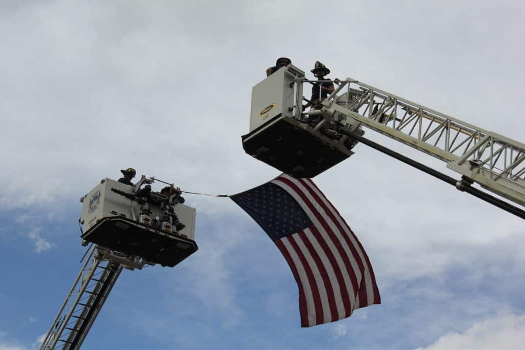 Emergency service personnel hang a flag between two fire truck ladders at the end of the First Responder Memorial convoy that runs from Ford Park in Vail to Freedom Park in Edwards. This year, the ceremonies will be closed to the public, but people are encouraged to gather along the procession route.