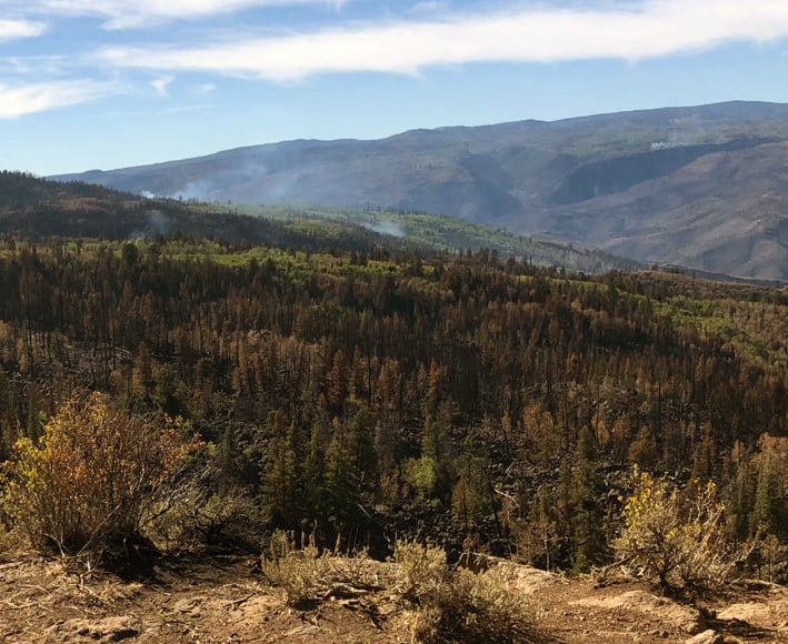 Smoke is visible in the Ike Creek drainage on Saturday.
