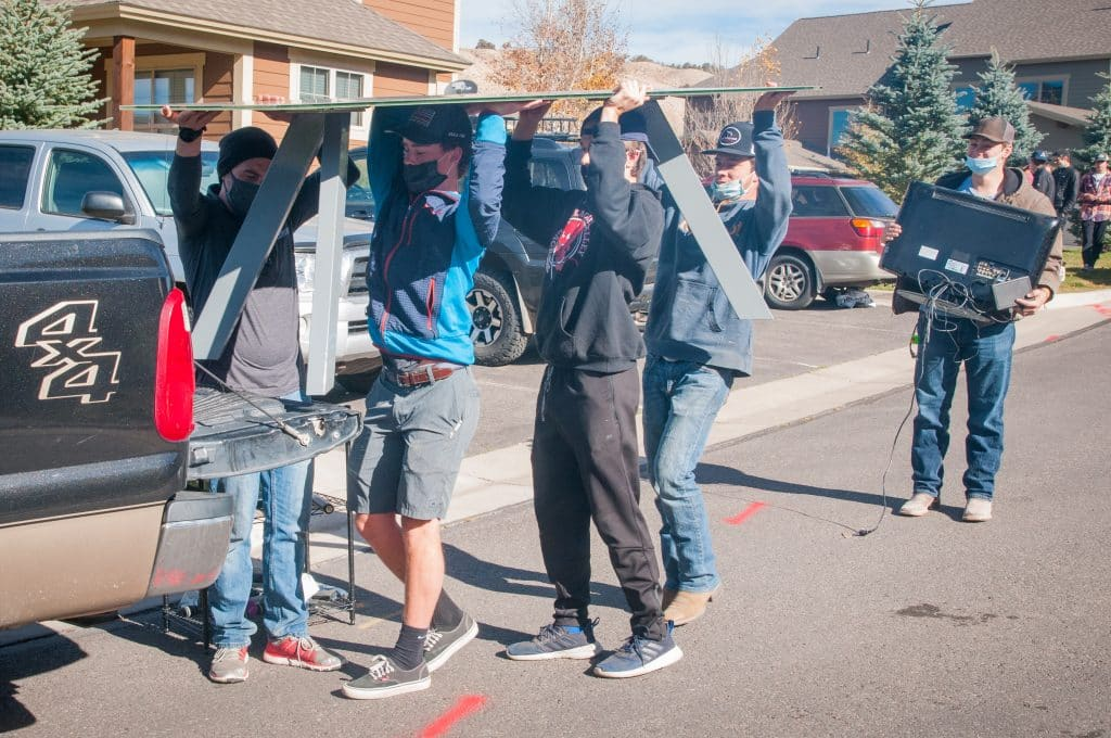 Teamwork makes the dream work as members of the Batttle Mountain High School Huskies hockey team load up a table during their volunteer day that the home of former hockey mom Mindee Stevenson.