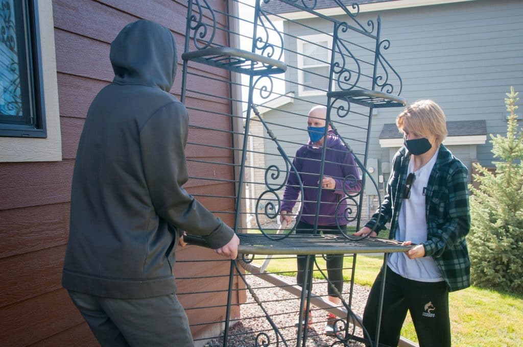 Mindee Stevenson directs members of the BMHS hockey team as they carry a shelf unit from her former home.